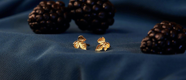 Vine Leaf Stud Earrings in gold plate on blue cloth with blackberries