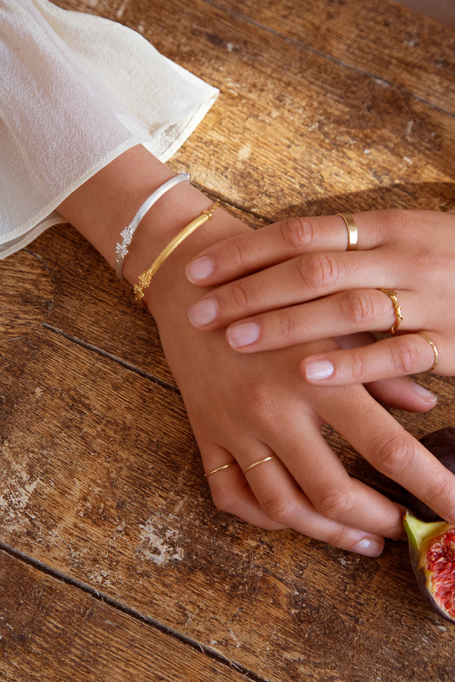 Model wears Fables Hinged Column Bracelet in silver and gold plate with overgrown vine ring and fine gold bands