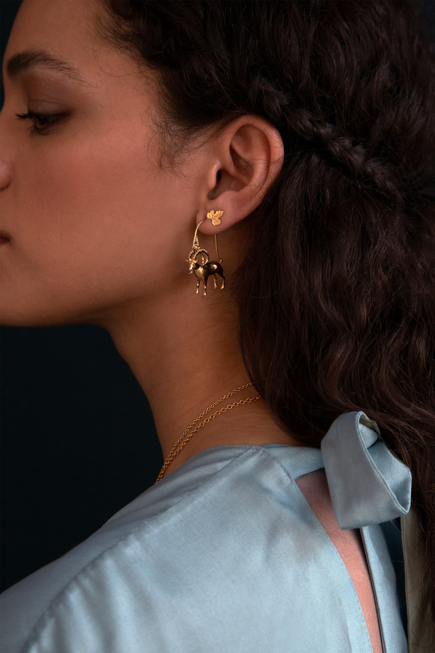 Model wears Fables Mountain Goat Creole Earrings in silver and gold plate