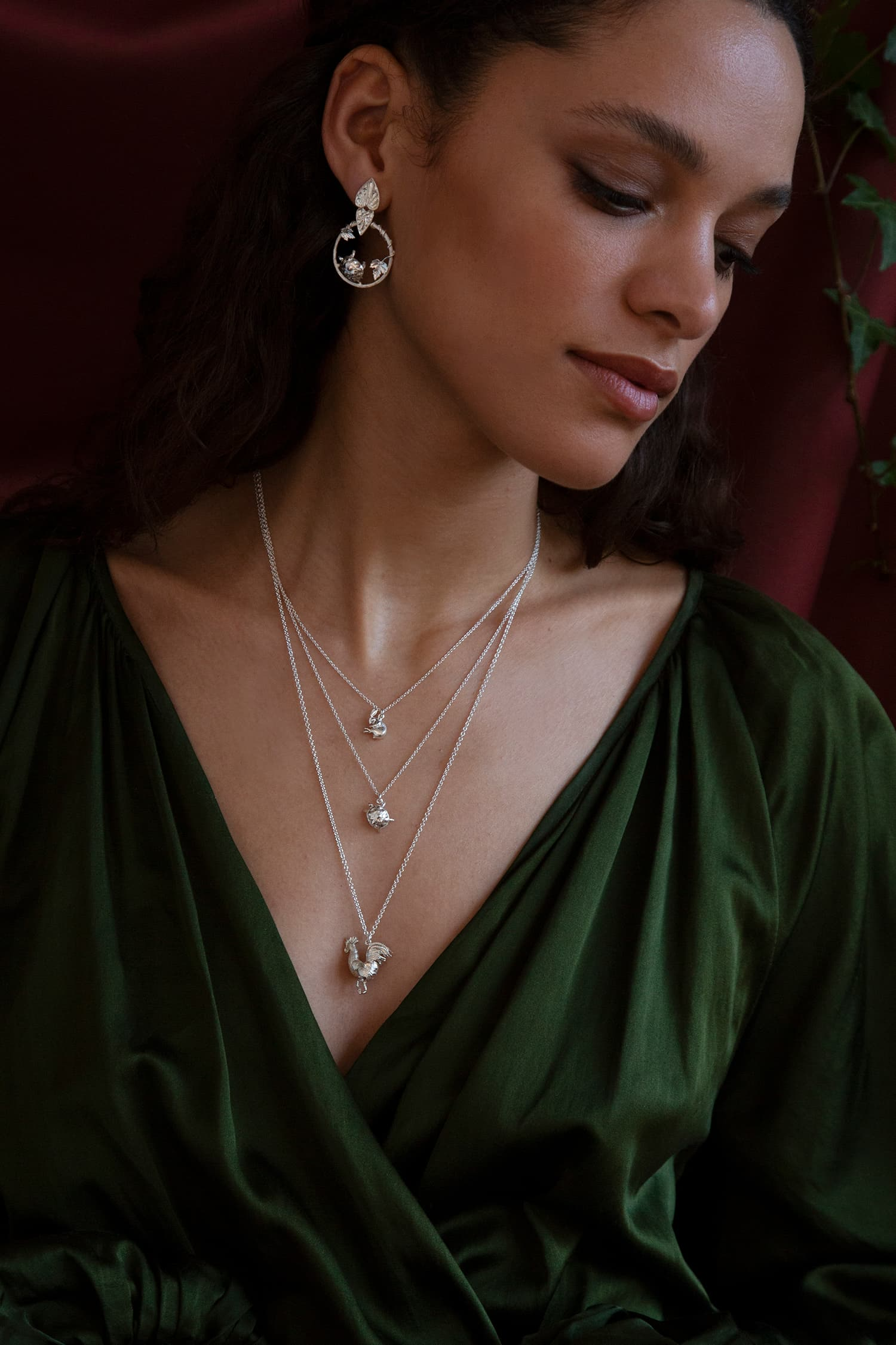 Model wears Fables silver necklaces and earrings featuring Hare and Tortoise, and a large rooster.