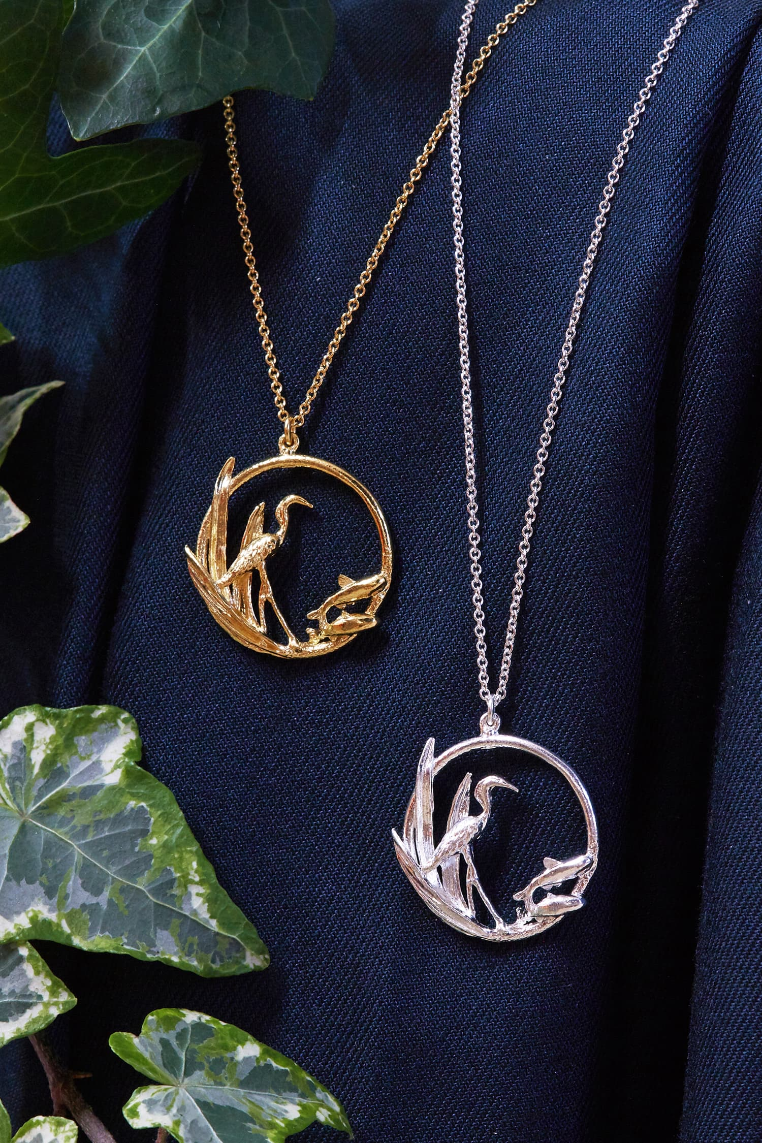 Two Heron & Fish Loop silver and gold plated necklaces hang against blue fabric with ivy