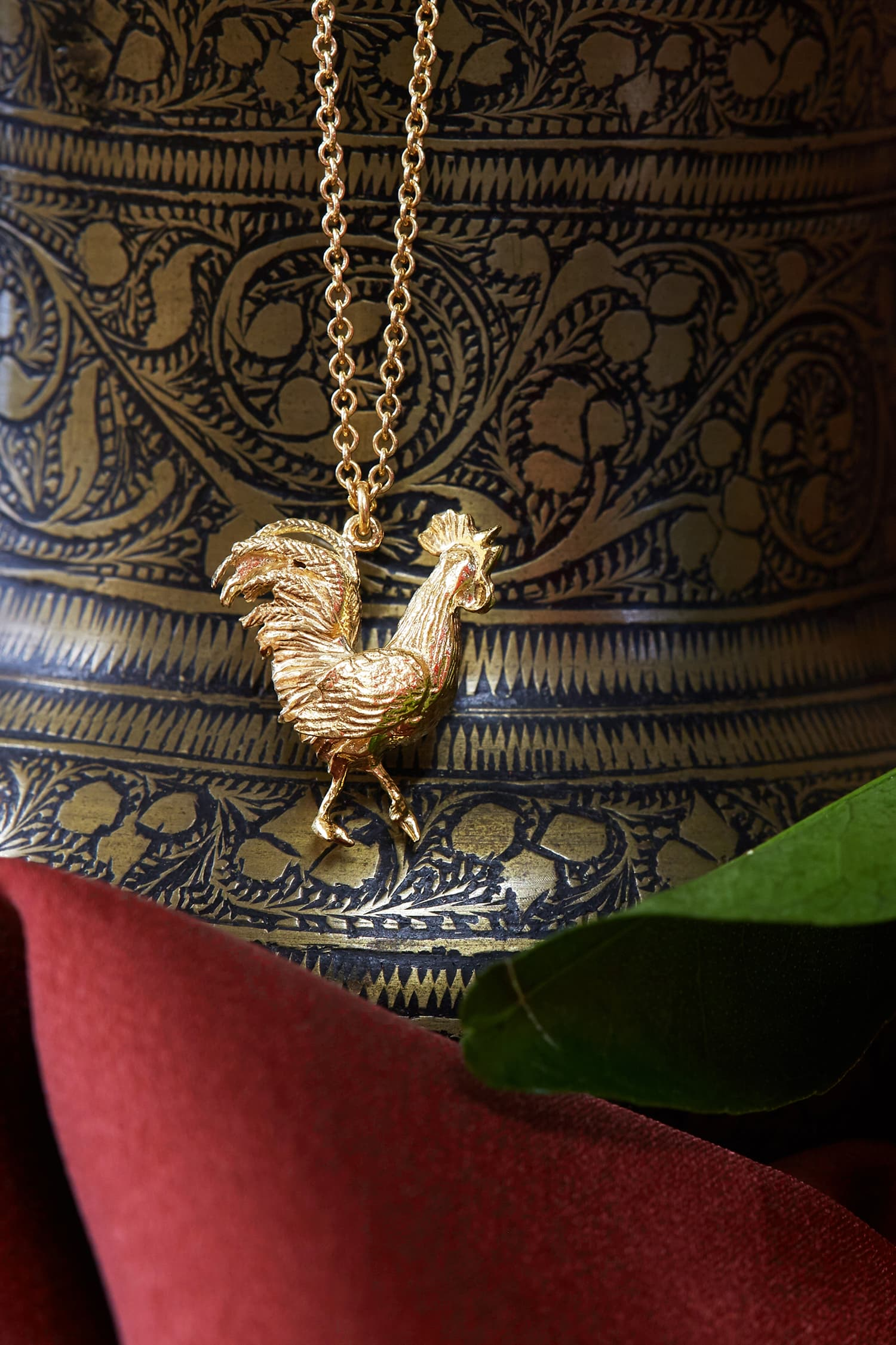 Gold plated Rooster necklace with organte illustrated background and green leaf