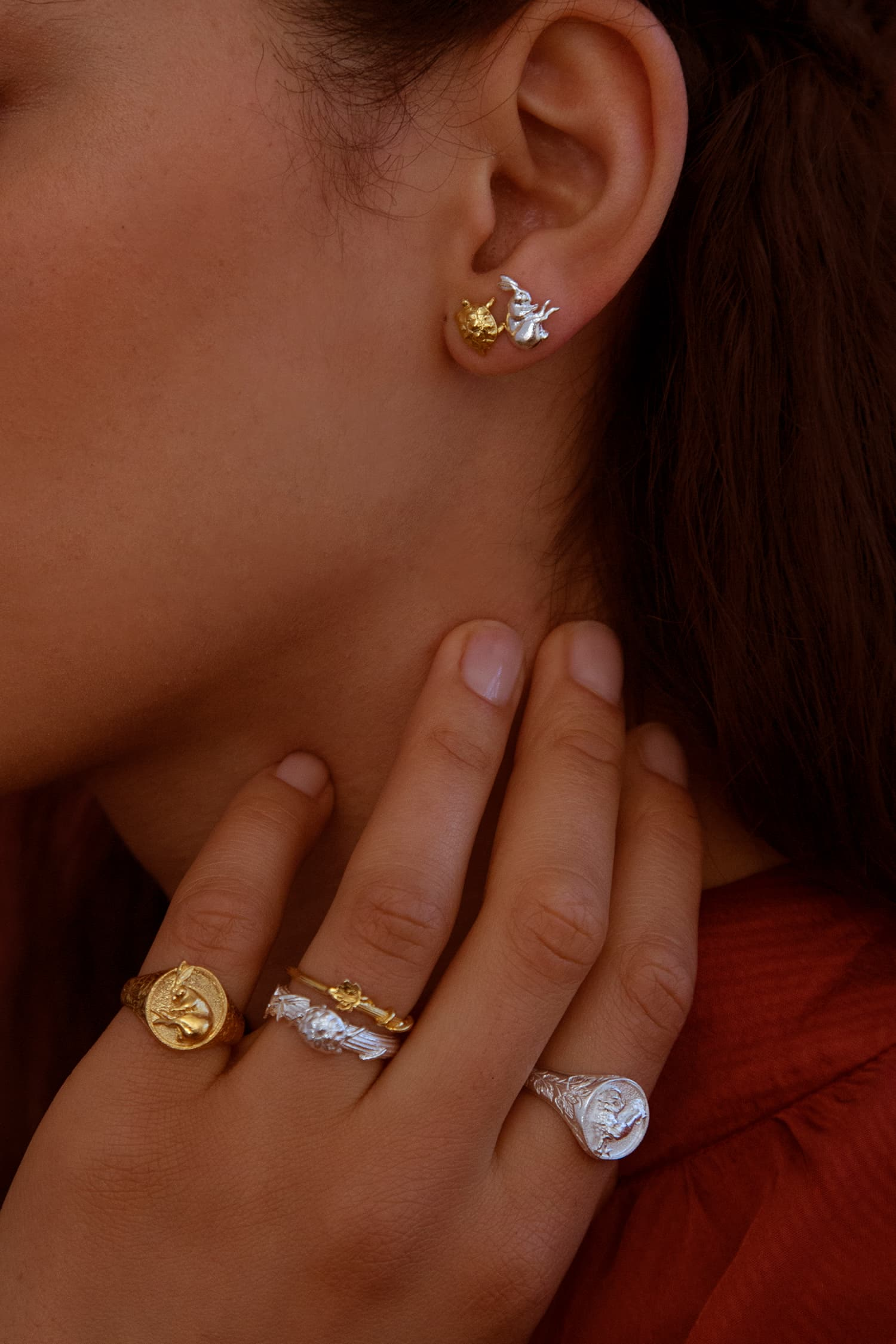 Model wears Fables Tortoise and Hare Stud earrings and selection of fables signet and fine column rings