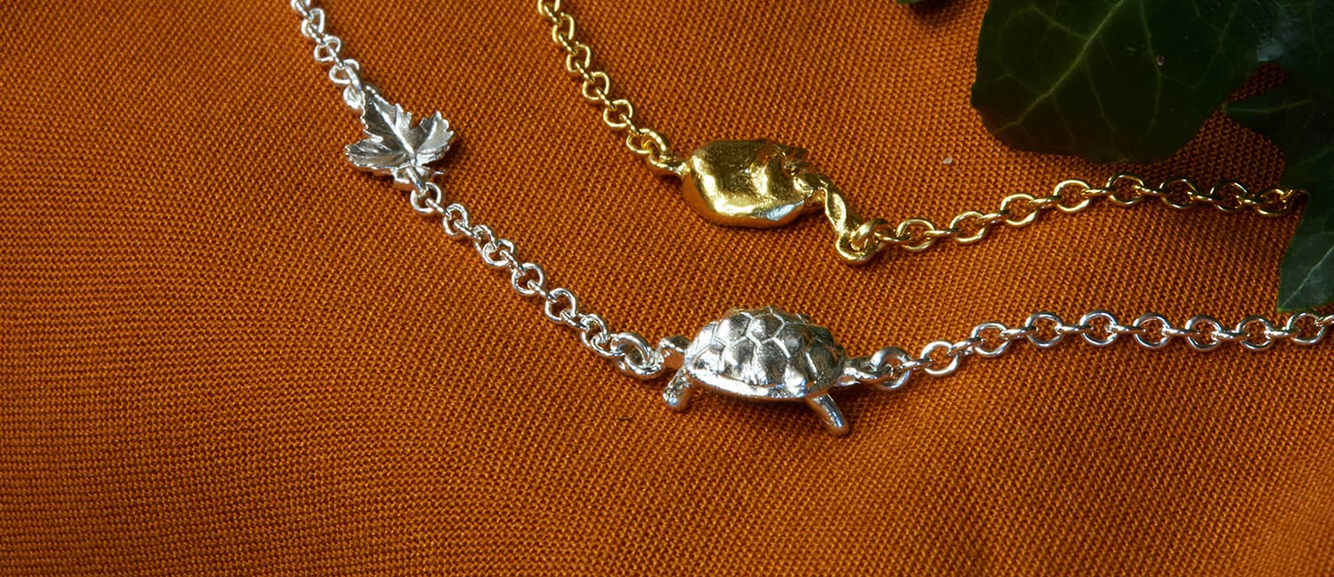 Hare and tortoise inline fairmined gold plated bracelets on rich orange fabric