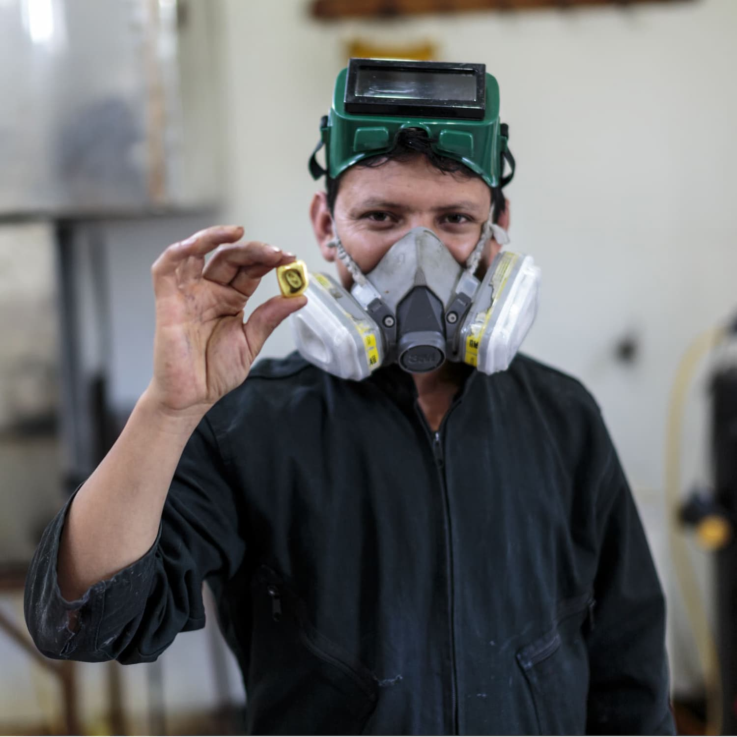 fairmined miner wearing breathing mask in workshop holding a piece of fairmined gold nugget