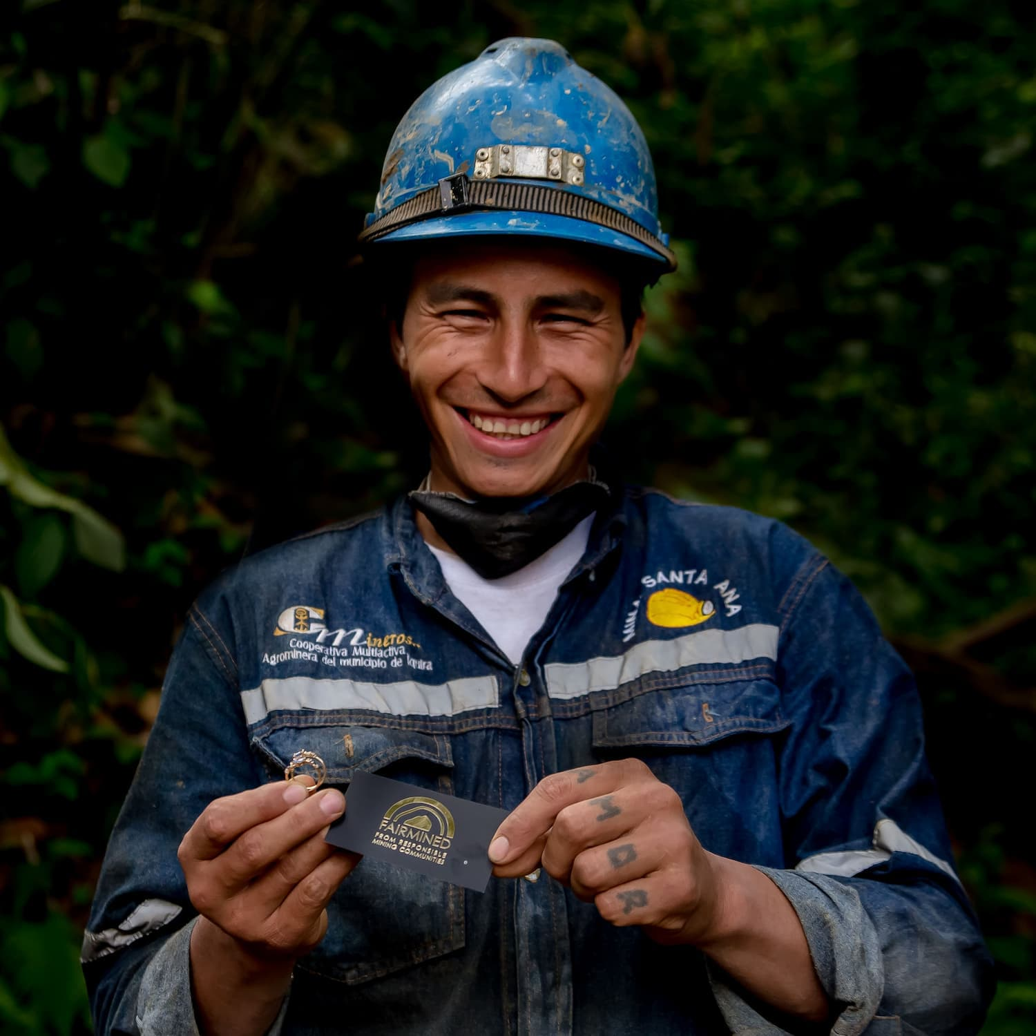 Fairmined Gold Miner wearing blue hard hat and overall and smiling holding fairmined gold rings