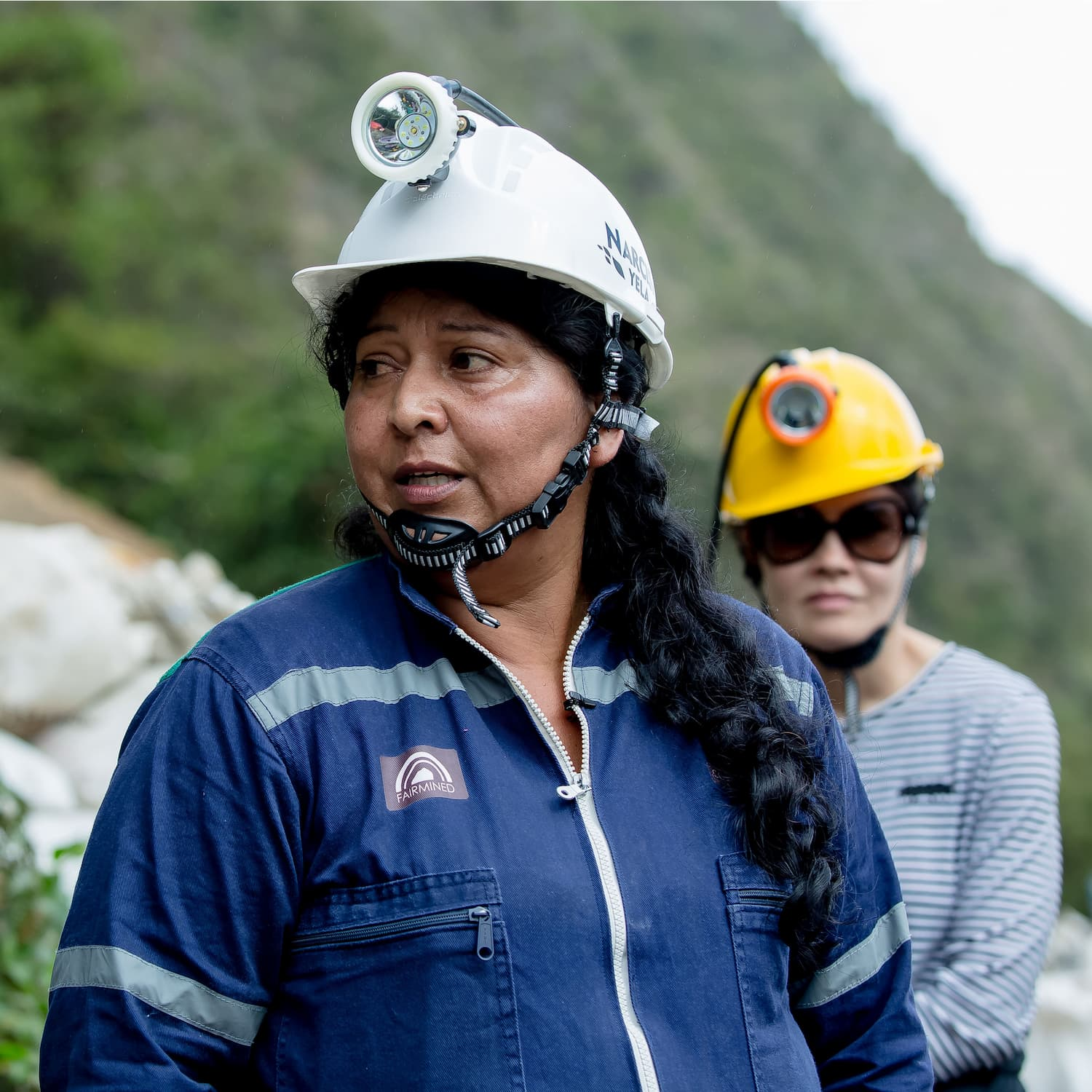 fairmined gold woman miner wearing hard hat with lamp and blue overall