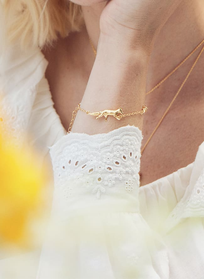 gold plated inline fox bracelet worn by model in white detailed top