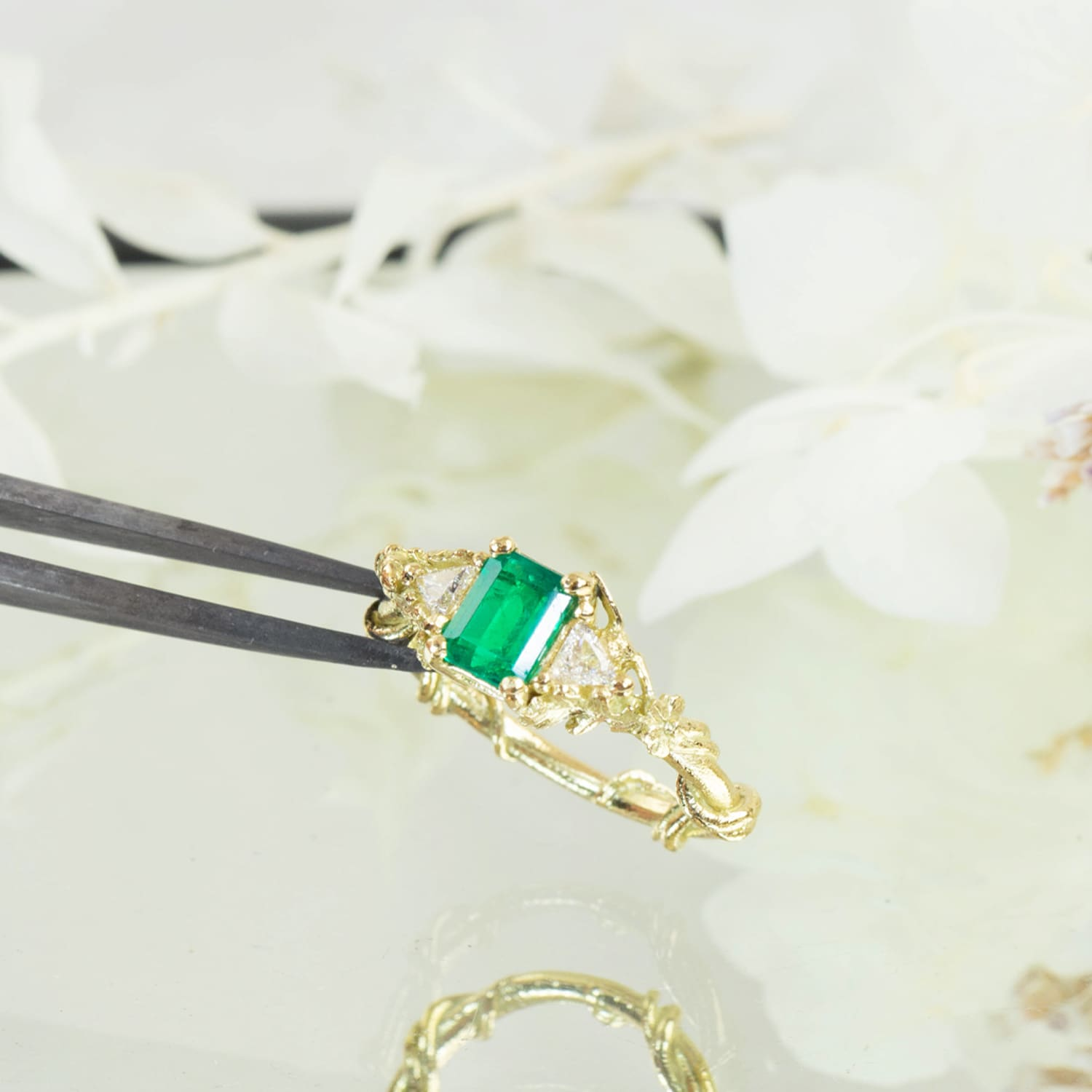 emerald gemstone 18ct yellow gold bespoke design engagement ring shown held in jewellers pliers against white petals