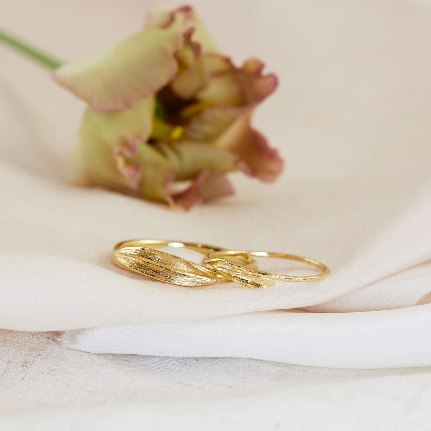 pair of 18ct yellow gold wedding bands rings with fine reed details on silk with flower petals
