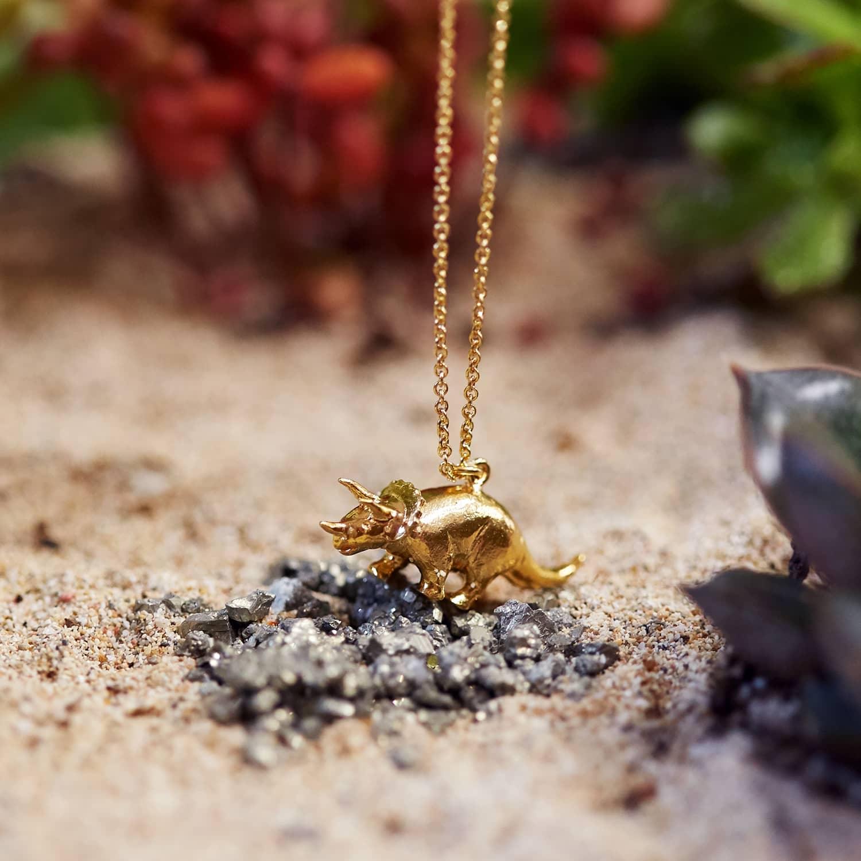 yellow gold triceratops dinosaur necklace in prehistoric scene