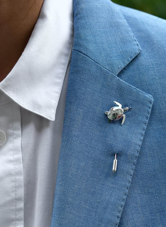 silver sea turtle lapel tie pin worn on blue suit jacket with white shirt